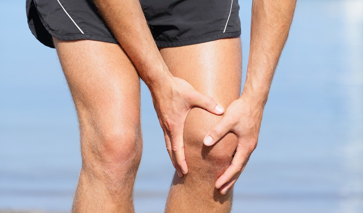 A runner holding his knee in pain